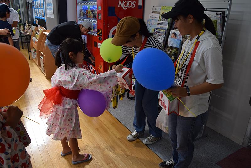 子どもに風船をプレゼントしている写真